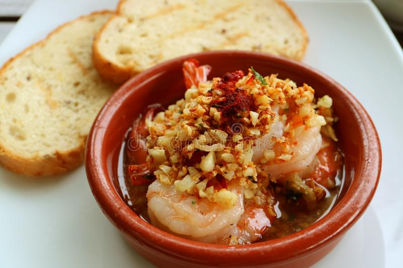 Delicious Spanish Style Garlic Shrimp or Gambas al Ajillo with Blurry Sliced Breads in Background royalty free stock images
