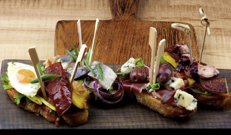 Delicious Spanish Tapas. Arrangement of Delicious Spanish Tapas with Chorizo and Fried Egg, Marinated Sardines and Red Onion, Jamon and Red Olives, Cooked royalty free stock photo