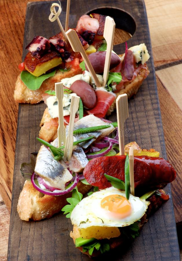 Delicious Spanish Tapas. Assorted Delicious Spanish Tapas with Chorizo and Fried Egg, Marinated Sardines and Red Onion, Jamon and Red Olives, Cooked Octopus and royalty free stock images