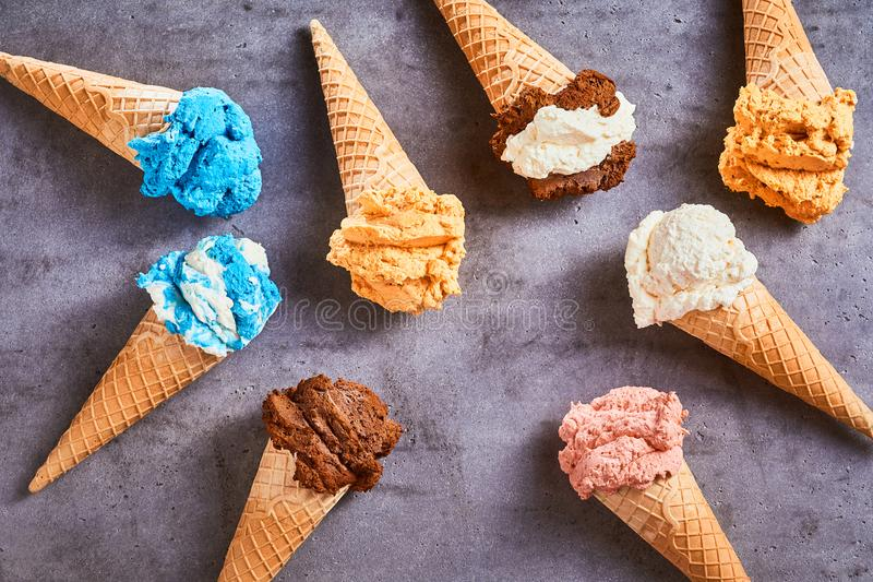 Delicious speciality ice cream cones. With a variety of different flavors arranged as a still life on a grey slate background royalty free stock images