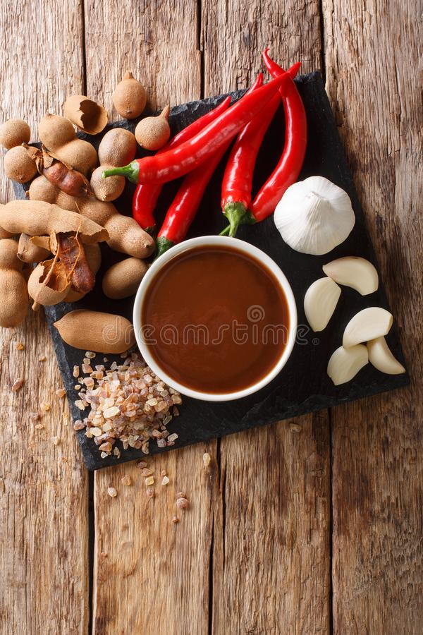 Delicious spicy tamarind sauce closeup in a bowl on a table. Vertical top view stock photo