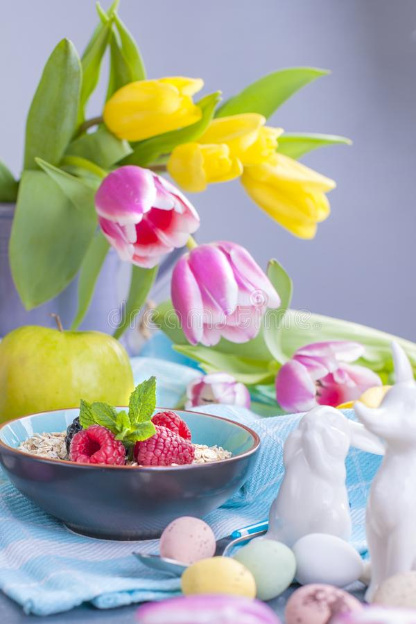 Delicious spring breakfast on a background of gray stone. Bouquet of fresh tulips. Small and large colored Easter eggs. Oatmeal, royalty free stock image