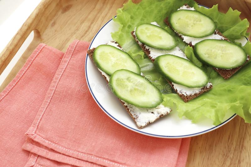 Delicious spring sandwiches with cream cheese, fresh cucumbers and salad leaves on a wooden board stock photo