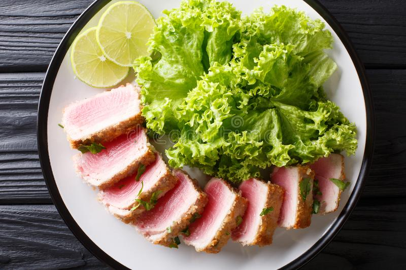 Delicious steak ahi tuna in bread crumbs panko with lettuce and. Lime closeup on a plate on a black table. horizontal top view from above royalty free stock photo