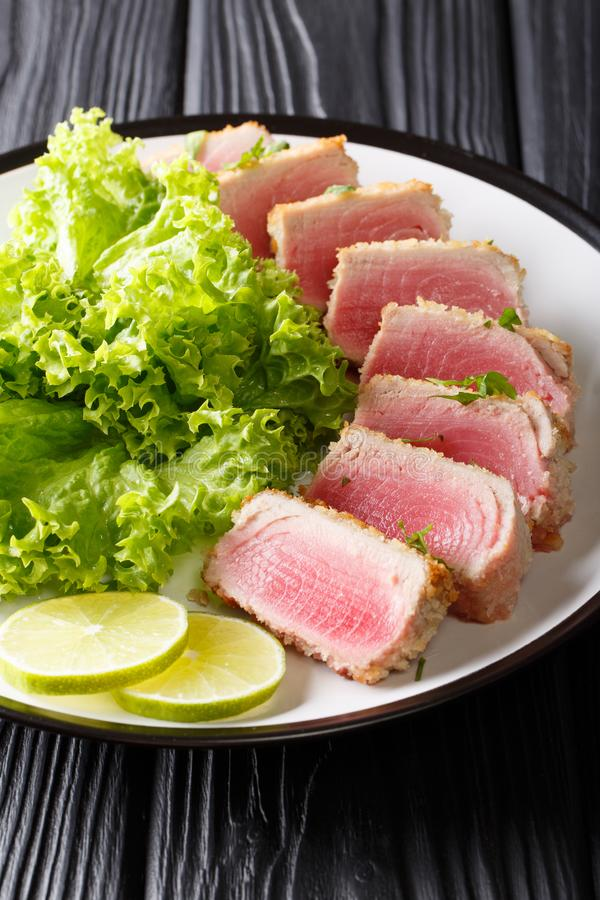 Delicious steak ahi tuna in bread crumbs panko with lettuce and. Lime closeup on a plate on a black table. vertical stock photos