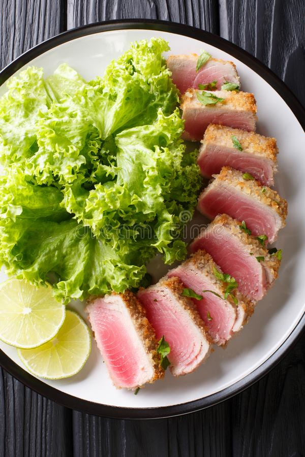 Delicious steak ahi tuna in bread crumbs panko with lettuce and. Lime closeup on a plate on a black table. Vertical top view from above stock photo
