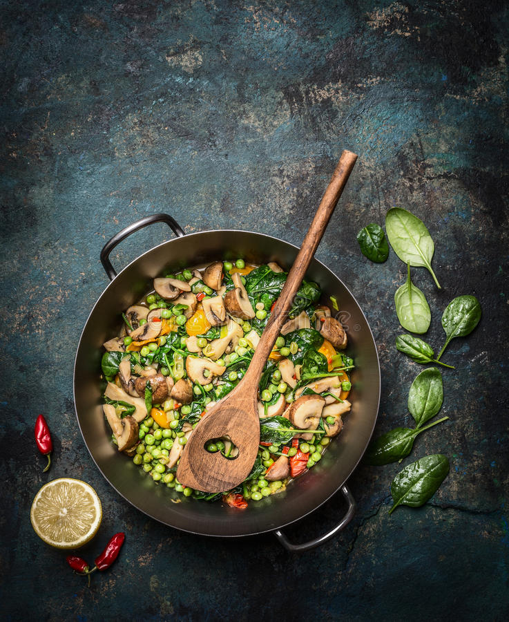 Delicious steamed healthy vegetables in cooking pan with ingredients and wooden spoon on dark rustic background, top view. stock photo