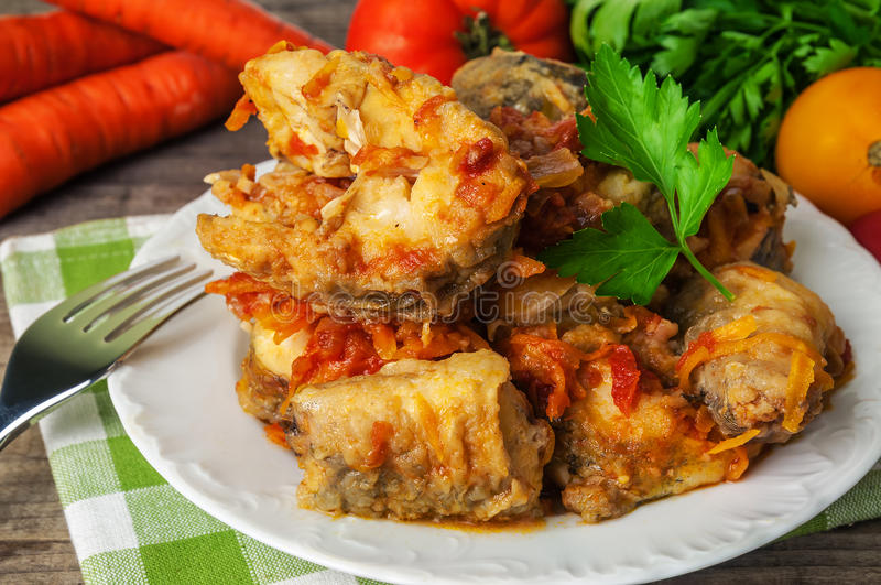 Delicious stewed fish. With carrots and tomato royalty free stock images