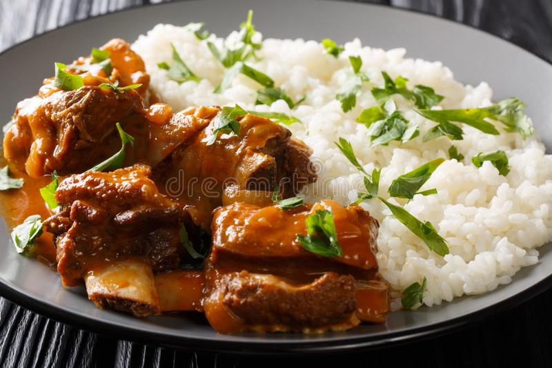 Delicious stewed ribs in a spicy sauce served with white rice close-up on a plate. horizontal royalty free stock image