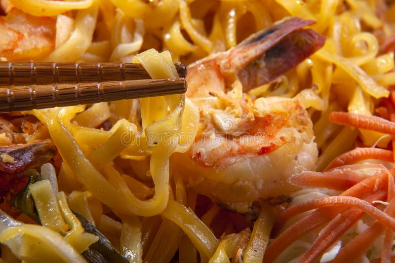 Pad Thai Noodles on a Plate with Chopsticks. Delicious stir fried noodles called pad thai in thailand is a tasty dish. It is made with seafood such as shrimp or royalty free stock photography
