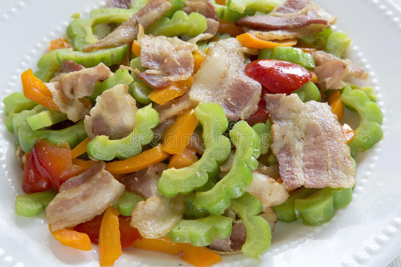 Delicious stir-fry bacon and bitter melon. Delicious stir-fry bacon ,bitter melon and sweet pepper on dish stock photo