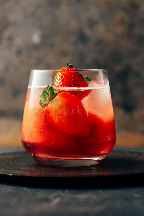 Delicious strawberry cocktail with ice on dark background royalty free stock photos