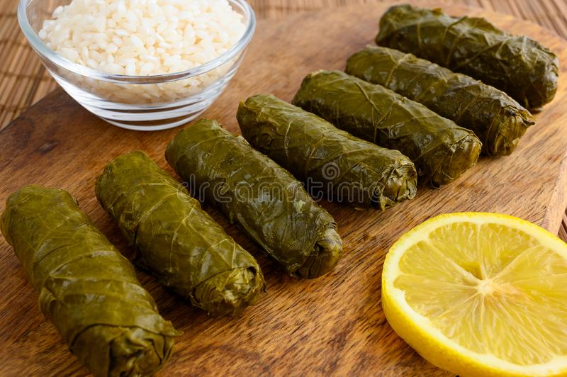 Stuffed grape leaves. Delicious stuffed grape leaves the traditional dolma of the mediterranean cuisine on wooden cutting board with lemon slice and small glass stock photos
