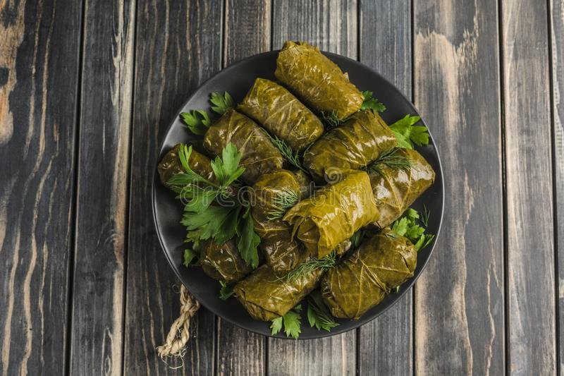 Delicious stuffed grape leaves traditional doom Mediterranean cuisine Dolma on a black plate with fresh cilantro and dill royalty free stock photo