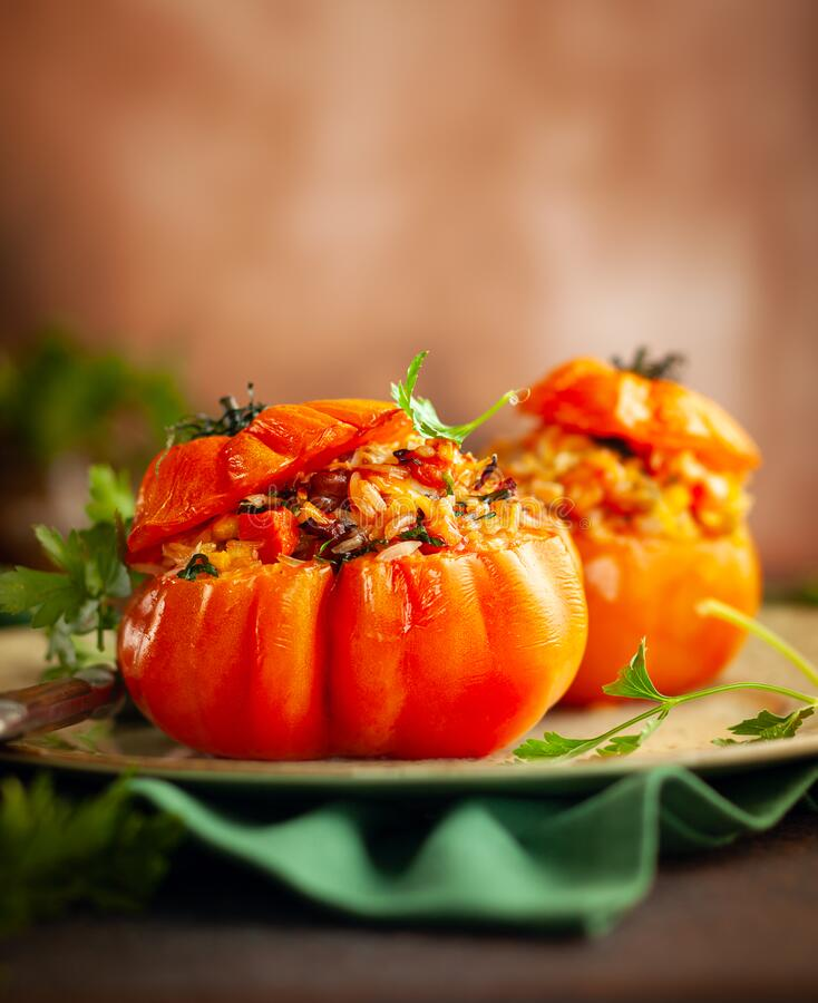 Delicious stuffed tomatoes in shape of pumpkin with rice, vegetables and meat. Concept homemade healthy eating royalty free stock photography