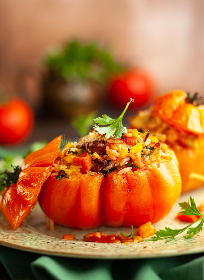Delicious stuffed tomatoes in shape of pumpkin with rice, vegetables and meat. Concept homemade healthy eating stock photography