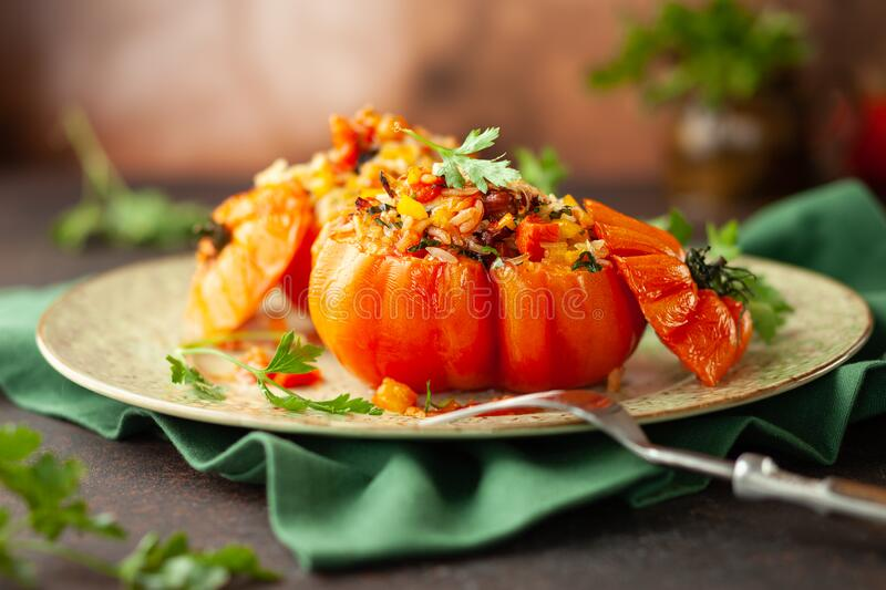 Delicious stuffed tomatoes in shape of pumpkin with rice, vegetables and meat. Concept homemade healthy eating stock images