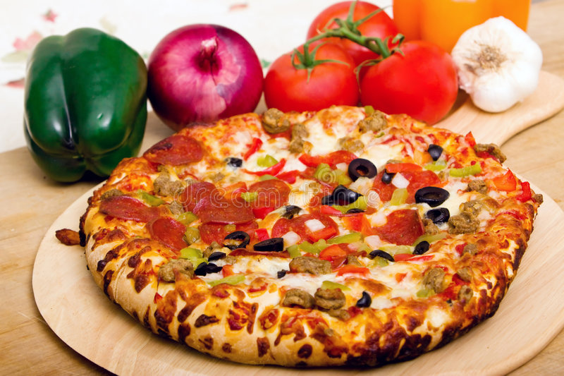 Delicious supreme pizza. With meat and vegetables royalty free stock image