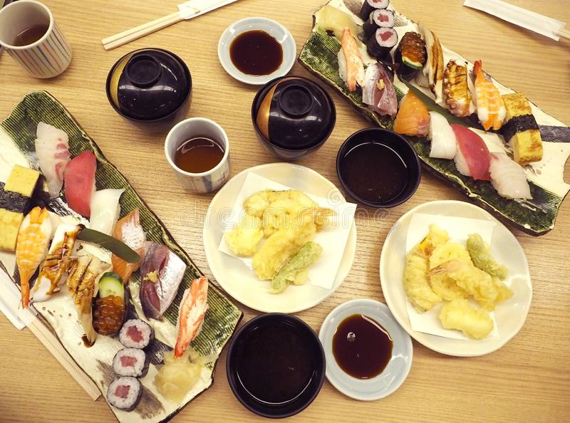 Assorted sushi, tempura sashimi and miso soup was presented beautifully on the wooden table in a Japanese restaurant stock images