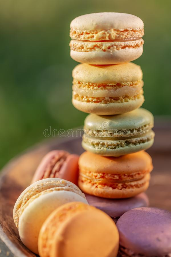 Delicious sweet airy colored french pastries. Sweets macarons for dessert in the summer evening. In the orchard. Natural blurred background. Image in soft focus stock photos