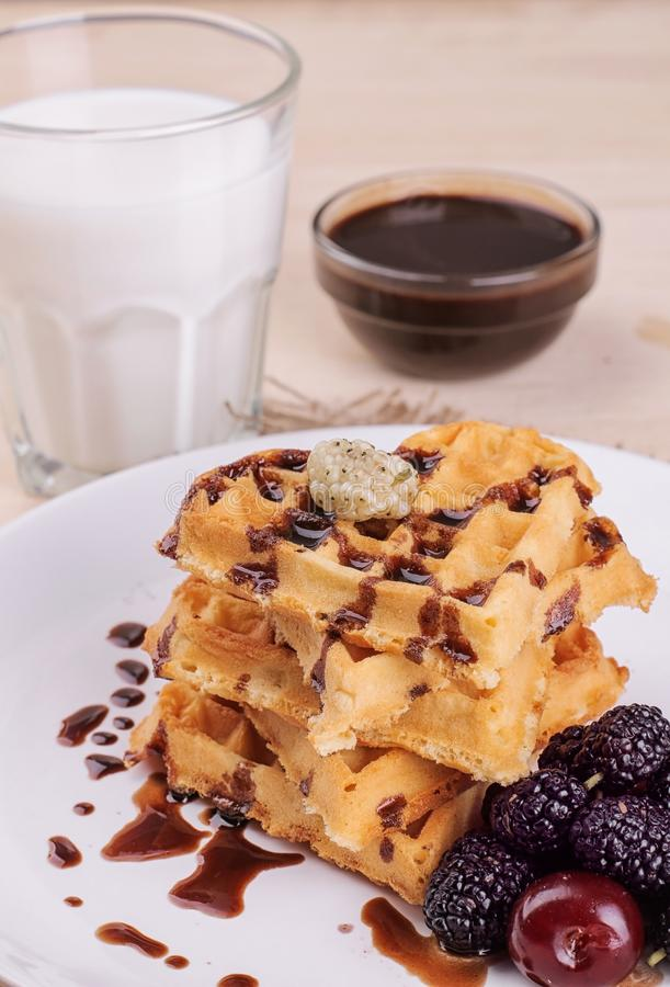 sweet Belgian waffles in the form of hearts with chocolate and berries with a glass of milk. breakfast. on a natural wooden backg stock image