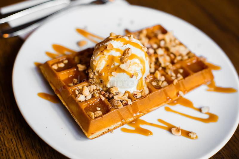 Delicious sweet belgian waffles with tasty white ice cream with caramel and nuts. Side close-up view. stock photo