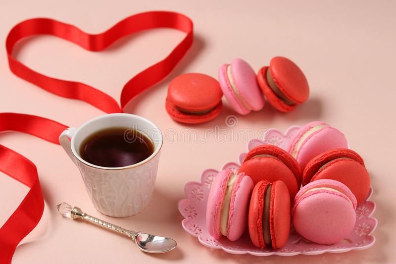 Delicious sweet macaroons in a figural plate on a pink background, red and pink macaroons. Concept for Valentine`s Day, Birthday, March 8 and Mother`s Day stock images