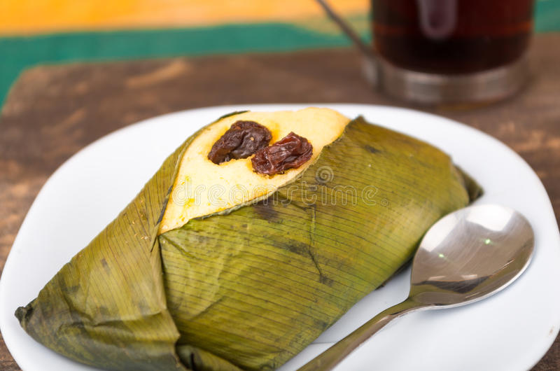 Delicious sweet rough with raisins wrapped in achira leaf served on a white dish, quimbolito. Of Ecuador stock images