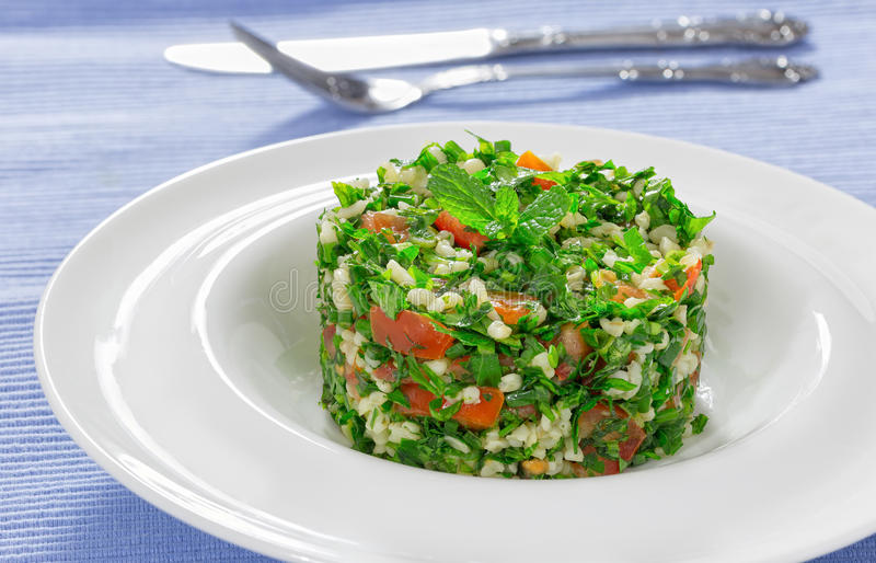 Delicious tabbouleh or parsley, peppermint, spring onion, tomato. Salad, drizzled with lemon juice and olive oil, decorated with mint leaves on white dish royalty free stock photography