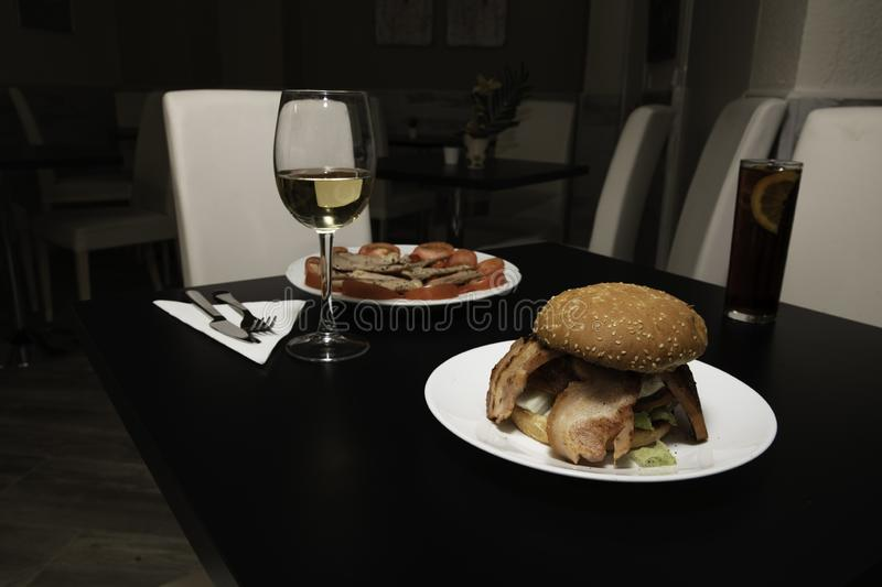 Delicious table set to eat, a delicious burger with a glass of wine and another dish more. Table ready to eat a delicious hamburger with an exquisite glass of stock image