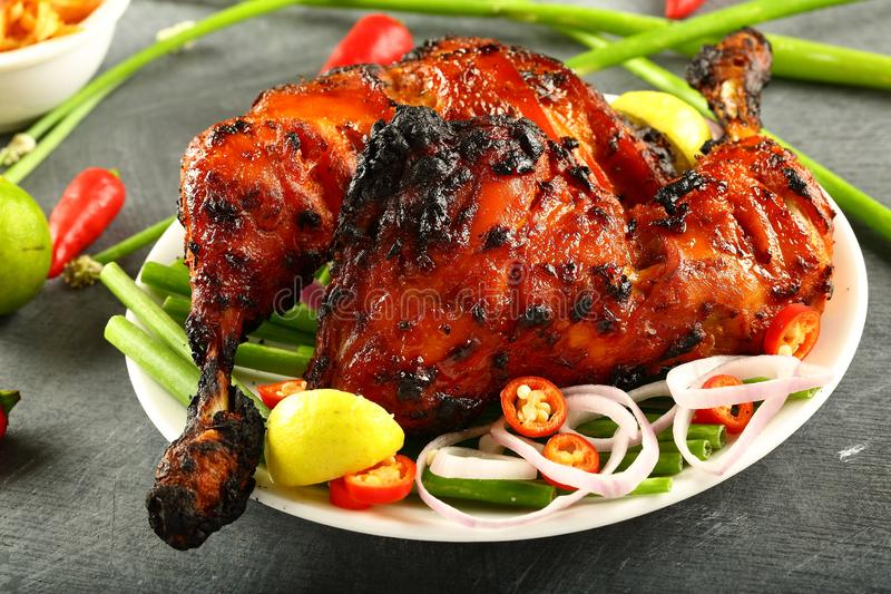 Delicious tandooti chicken with salads. Delicious homemade tandoori chicken with salads on a dark background stock photography