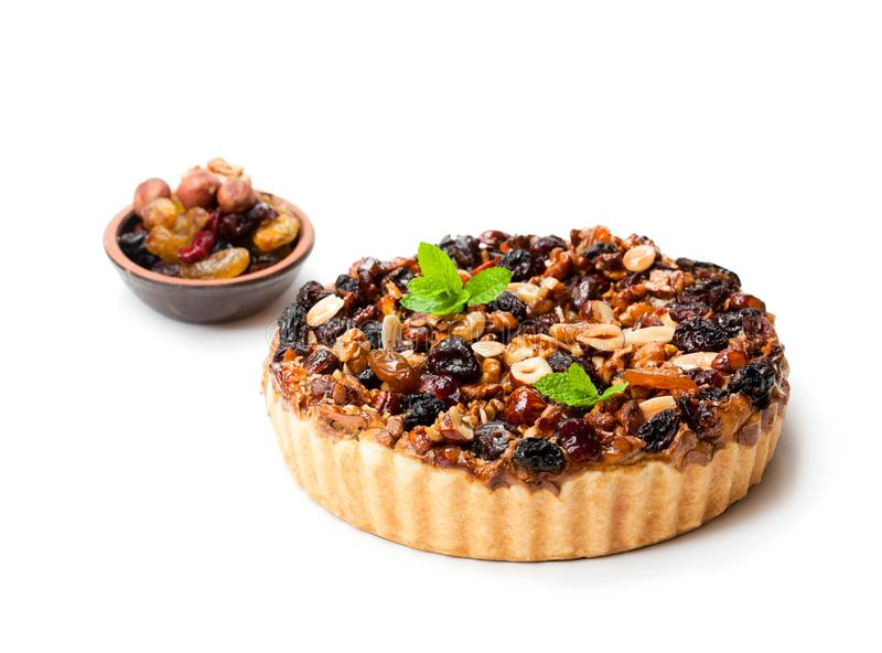Delicious tart with dried berries and nuts isolated on white royalty free stock photography