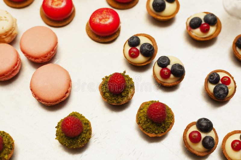 Delicious tartelets filled with fruits macarons stock photography