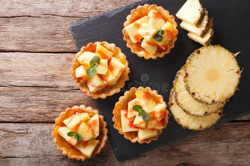 Delicious tartlets with fresh pineapple and jam closeup on the t. Able. Horizontal view from above royalty free stock photo