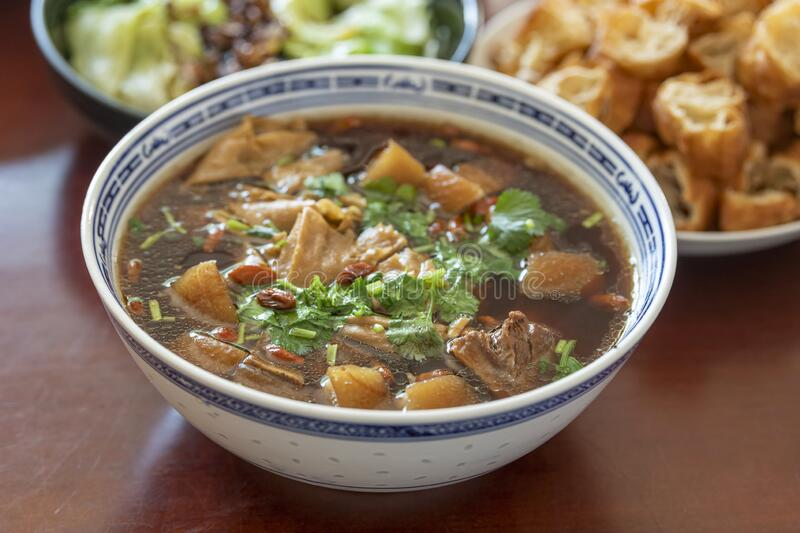 Delicious and tasty Bah Kut Teh pork rib soup served with stir ice salad and fried onion plus fired bread. This a typical royalty free stock photography