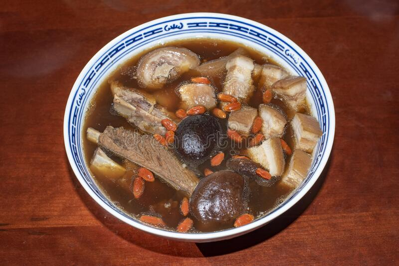 Delicious and tasty Bah Kut Teh pork rib soup served with stir ice salad and fried onion plus fired bread. This a typical royalty free stock photos