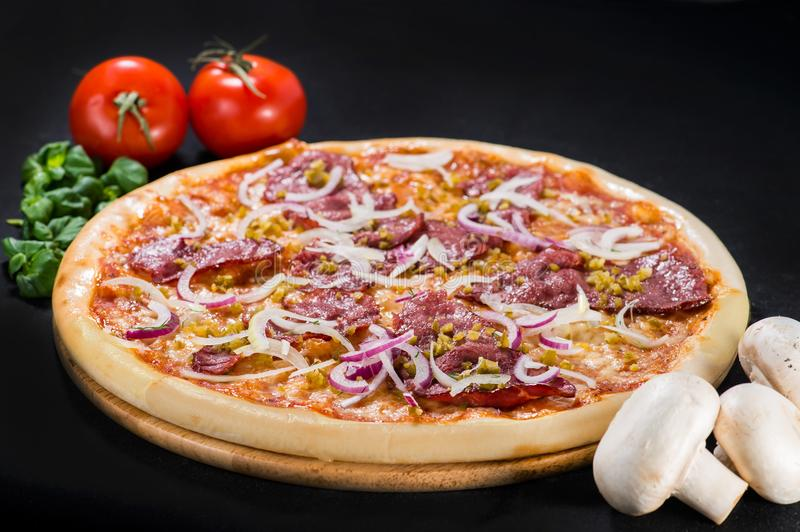 Delicious tasty Diablo pizza with mozzarella, beef, onion, pepper and sauce on wooden board on dark background stock images