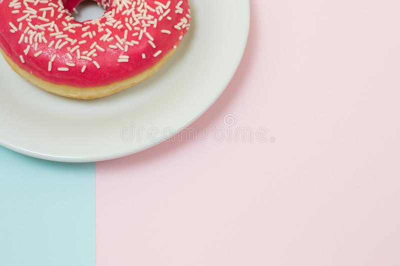 Delicious tasty glazed bright pink donut on blue and pink background, top view, close up, minimal style, soft color, copyspace royalty free stock photo