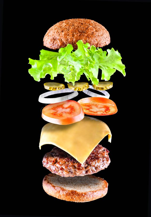 Delicious tasty hamburger with flying ingredients isolated on black background. Burger parts flying in air. Floating stock image