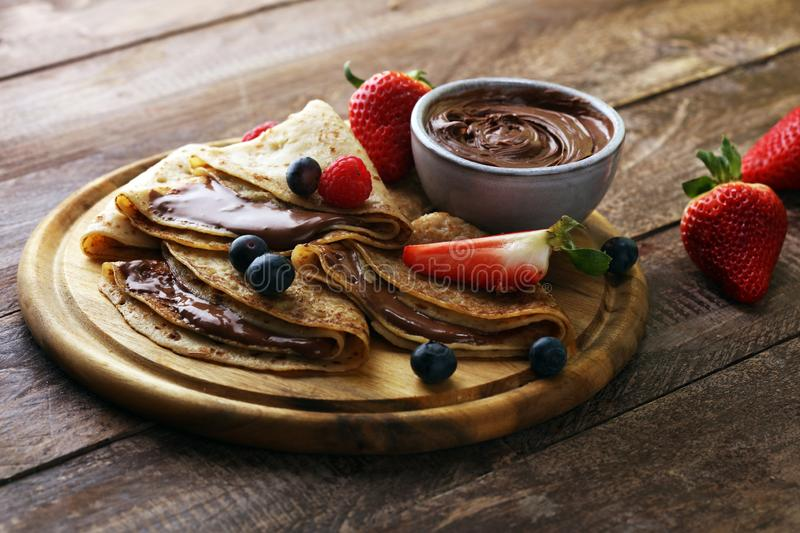 Delicious Tasty Homemade crepes with chocolate or pancakes with raspberries and blueberries on rustic wood. Delicious Tasty Homemade crepes with chocolate or stock photography