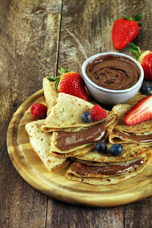 Delicious Tasty Homemade crepes with chocolate or pancakes with raspberries and blueberries on rustic wood. Delicious Tasty Homemade crepes with chocolate or royalty free stock image