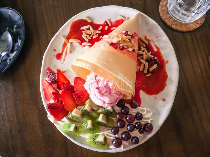 Delicious Tasty Homemade crepes with Strawberry ice cream with strawberries, kiwi, grape royalty free stock photos