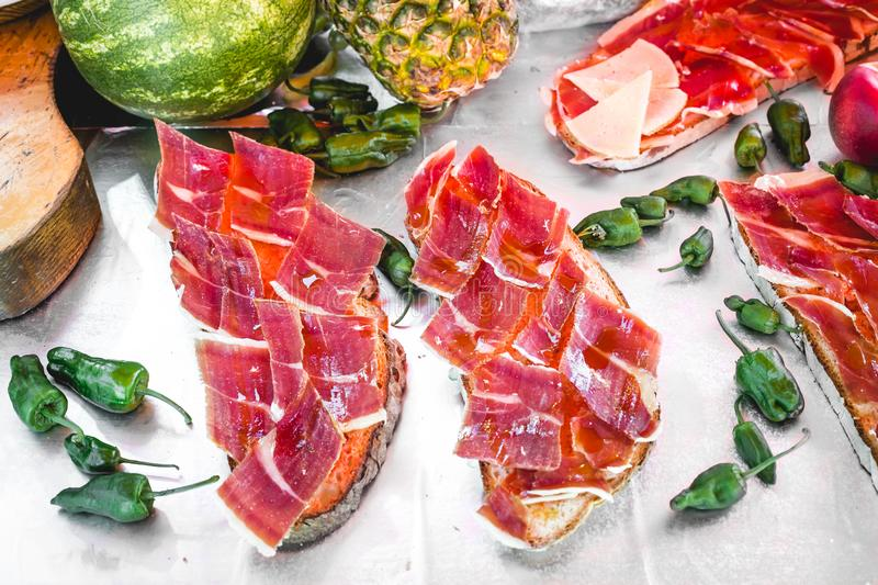 Delicious tasty street food at a market in Spain. Iberian ham toast with tomato stock photography