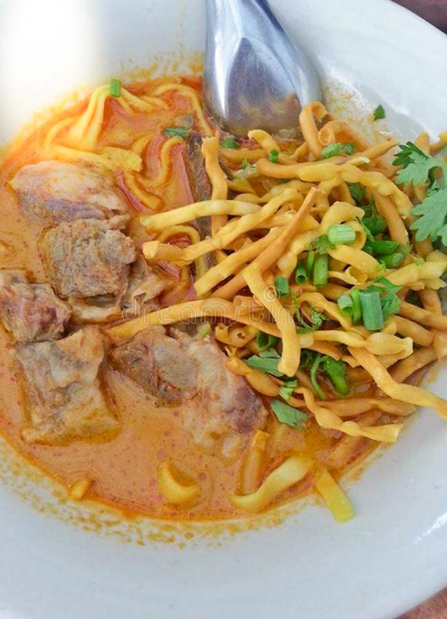Delicious tasty Thai Northern Style Curried Noodle Soup with Beef in a bowl Khao Soi, Northern Thailand Food background close up stock photo