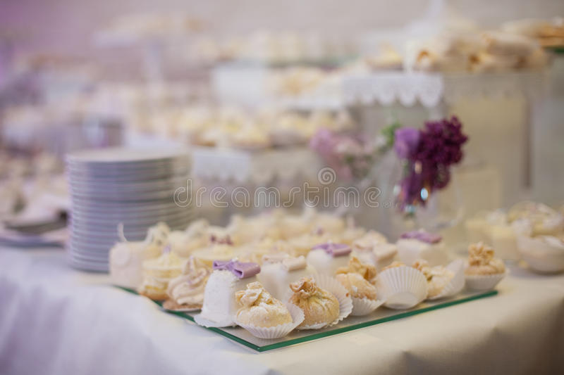 Delicious & tasty white decorated cupcakes at wedding reception. Closeup stock photo