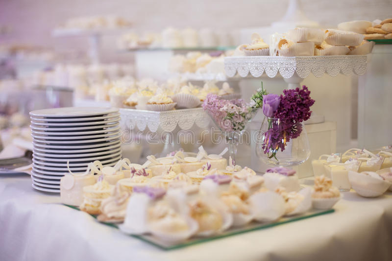Delicious & tasty white decorated cupcakes at wedding reception. Closeup stock photography