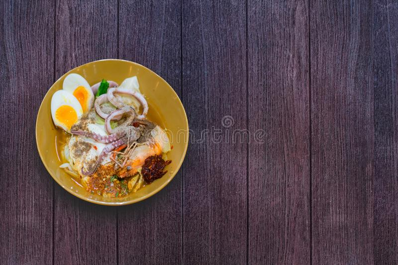Delicious Thai food. Noodle with hot and sour seafood prawn and squid soup with slice boiled egg and vegetable in brown bowl at. Cafe and restaurant on wooden royalty free stock photos