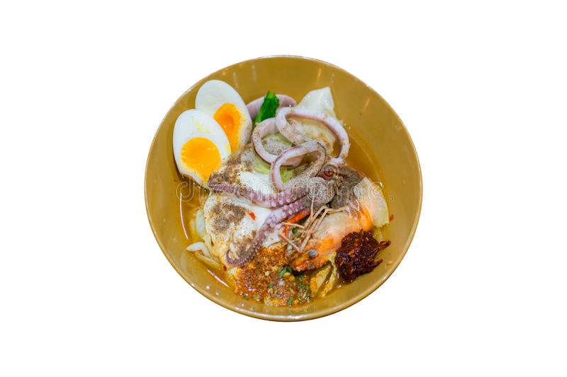 Delicious Thai food. Noodle with hot and sour seafood prawn and squid soup with slice boiled egg and vegetable in brown bowl. Isolated on white background royalty free stock photo