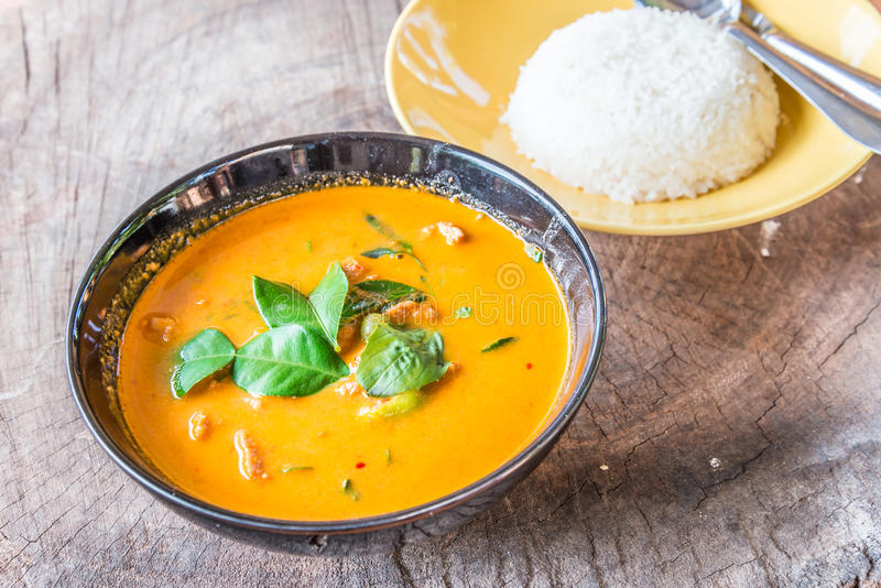 Delicious Thai panang curry and rice on wood background. stock image