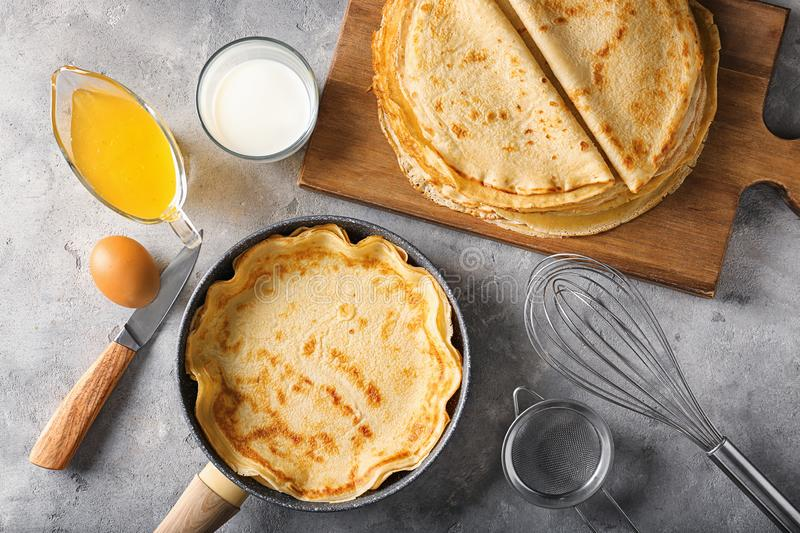 Delicious thin pancakes with glass of milk and honey on grunge table stock images